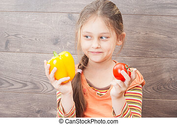 beautiful little girl holds fresh vegetables on a wooden backgro