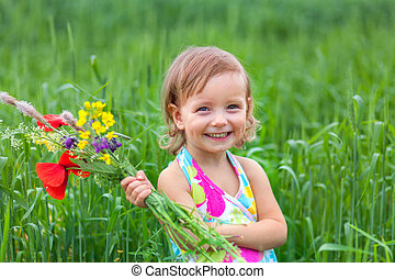 Beautiful little girl in a meadow with a bouquet of flowers