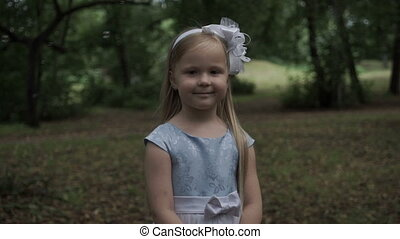 Beautiful little girl in a park on a background of soap bubbles