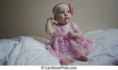 beautiful little girl in a pink dress sitting on a bed
