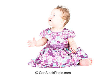Beautiful little girl in a purple dress, isolated on white