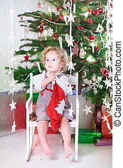 Beautiful little girl in a red dress checking her Christmas stoc