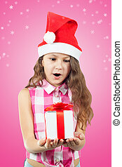 beautiful little girl in a Santa hat with a gift