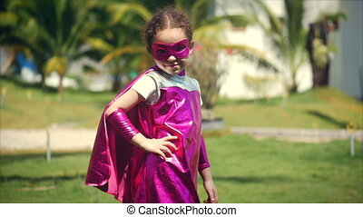Beautiful Little Girl in a Superhero Costume, Dressed in a Cloak and Mask of a Hero, Looking in camera. Concept of a Happy Childhood.