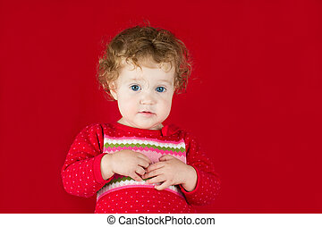 Beautiful little girl in a warm knitted sweater on red backgroun