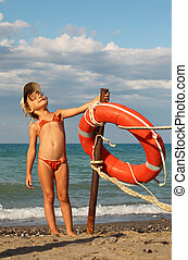 beautiful little girl in bathing suit and cap standing on beach. she clings to metal pole, on pole hanging red life buoy