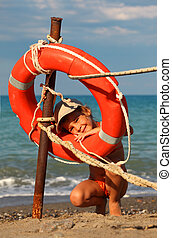 beautiful little girl in bathing suit and cap standing on beach, girl stuck her head into life buoy