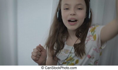 Beautiful little girl in headphones singing a song emotionally and dancing at window.