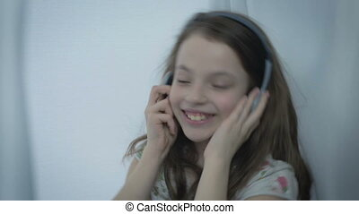 Beautiful little girl in headphones singing song emotionally and dancing