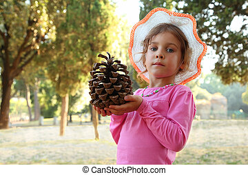beautiful little girl in pink blouse and hat holding big cone, focus on cone