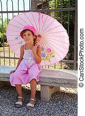 beautiful little girl in pink sarafan sitting on bench under pink umbrella