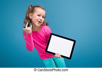Beautiful little girl in pink shirt with monkey and blue trousers hold empty tablet