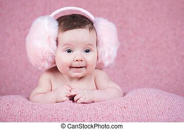 Beautiful little girl in pink warm headphones