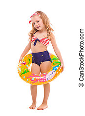 Beautiful little girl in red striped bikini, blue bottoms and pink wreath stand stand with colorful rubber ring on the waist