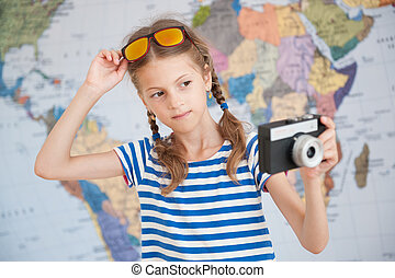 beautiful little girl in striped sailor shirt and sunglasses with vintage camere in hand on world map background