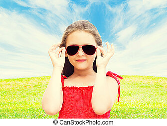 beautiful little girl in sunglasses on a green field with blue s
