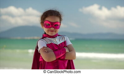 Beautiful Little Girl in the Superhero Costume, Dressed in a Pink Cloak and the Mask of the Hero. Plays on the Background Sea and Blue Sky and Clouds. Concept of a Happy Childhood.