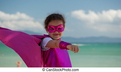 Beautiful Little Girl in the Superhero Costume, Dressed in a Pink Cloak and the Mask of the Hero. Plays on the Background Sea and Blue Sky and Clouds, Sends a Fist Forward. Concept of a Happy Childhood.