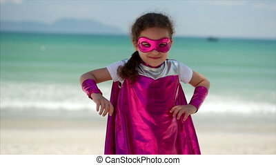 Beautiful Little Girl in the Superhero Costume, Dressed in a Pink Cloak and the Mask of the Hero. Plays on the Background Sea and Blue Sky and Clouds, Puts Hands on Belt. Concept of a Happy Childhood.