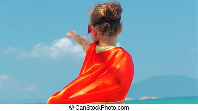 Beautiful Little Girl in the Superhero Costume, Dressed in a Red Cloak and the Mask of the Hero. Plays on the Background Sea and Blue Sky and Clouds, Sends a Fist Forward. Concept of a Happy Chilhood.