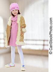 Beautiful little girl in winter coat with fur.