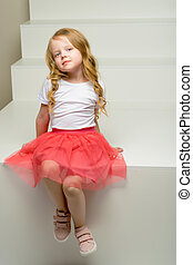 Beautiful little girl is sitting on the white staircase.