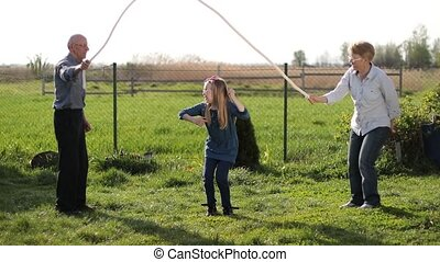 Beautiful little girl jumping over rope outdoors