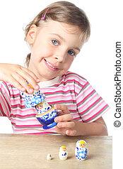 beautiful little girl keep blue matryoshka and smiling isolated on white