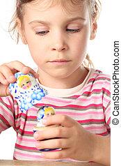 beautiful little girl keep blue matryoshka isolated on white