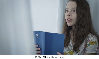 Beautiful little girl learns a poem by window. - Beautiful...