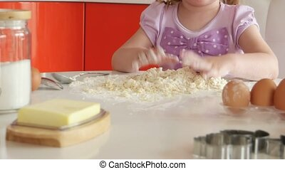 beautiful little girl learns to cook in the kitchen