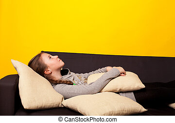 Beautiful little girl lies in a room on the couch