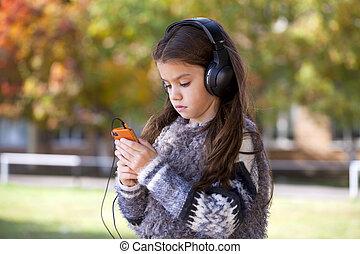 Beautiful little girl listening to music on headphones