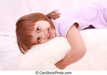 Beautiful little girl lying on bed