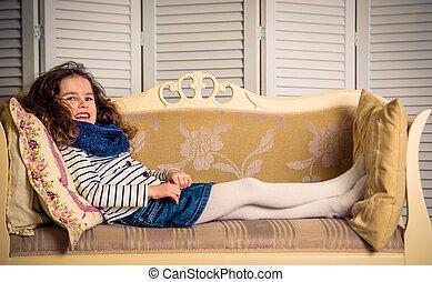 beautiful little girl lying on sofa