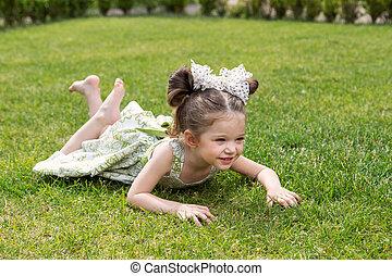 beautiful little girl lying on the grass