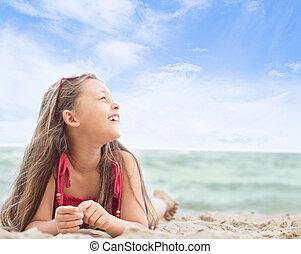 beautiful little girl lying on the sandy sea beach