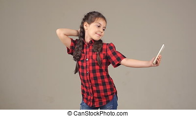 beautiful little girl making selfie. child posing for the camera. little lady with mobile phone in hand
