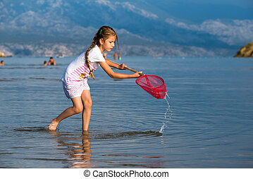 Beautiful little girl on the beach fishes