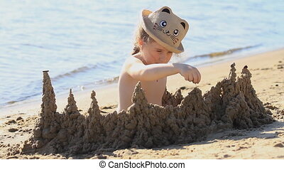 beautiful little girl on the river bank builds a sand castle