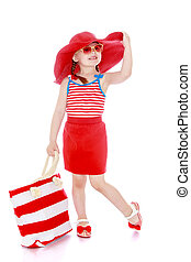 Beautiful little girl on vacation in a wide red hat and glasses