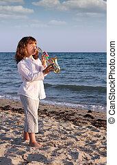 beautiful little girl play saxophone on beach