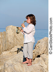 beautiful little girl play saxophone