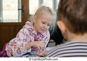 Beautiful little girl playing a game of checkers