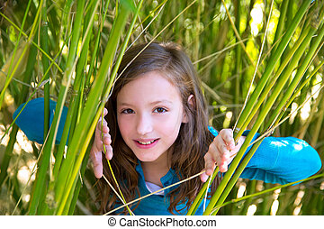 girl playing in nature  peeping from green canes