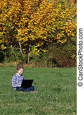 beautiful little girl playing laptop in the park autumn season