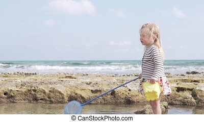 Beautiful little girl playing on the beach by the sea.