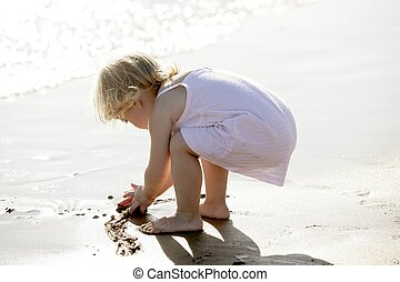 Beautiful little girl playing on the beach
