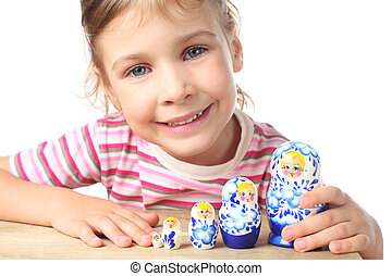 beautiful little girl playing with blue matryoshka and smiling isolated on white