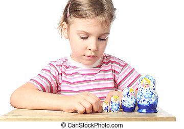 beautiful little girl playing with blue matryoshka isolated on white
